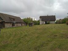 Talu kõrvalhoonete ja maaga.